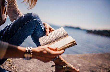 Woman reading book next to sea