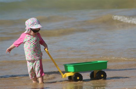 Small child pulling cart on the beach