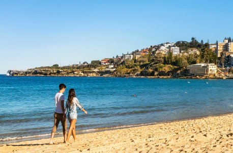 Man and woman holding hands on Coogee Beach