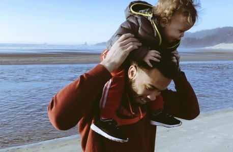 Little child riding on dads shoulders