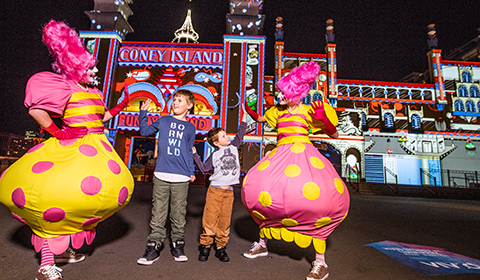 Street artists high-fiving children in front of the Spirit of Fun light installation at Luna Park during Vivid Sydney 2018.