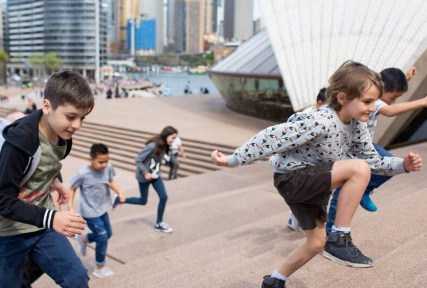 Kids climbing steps of Sydney Opera House